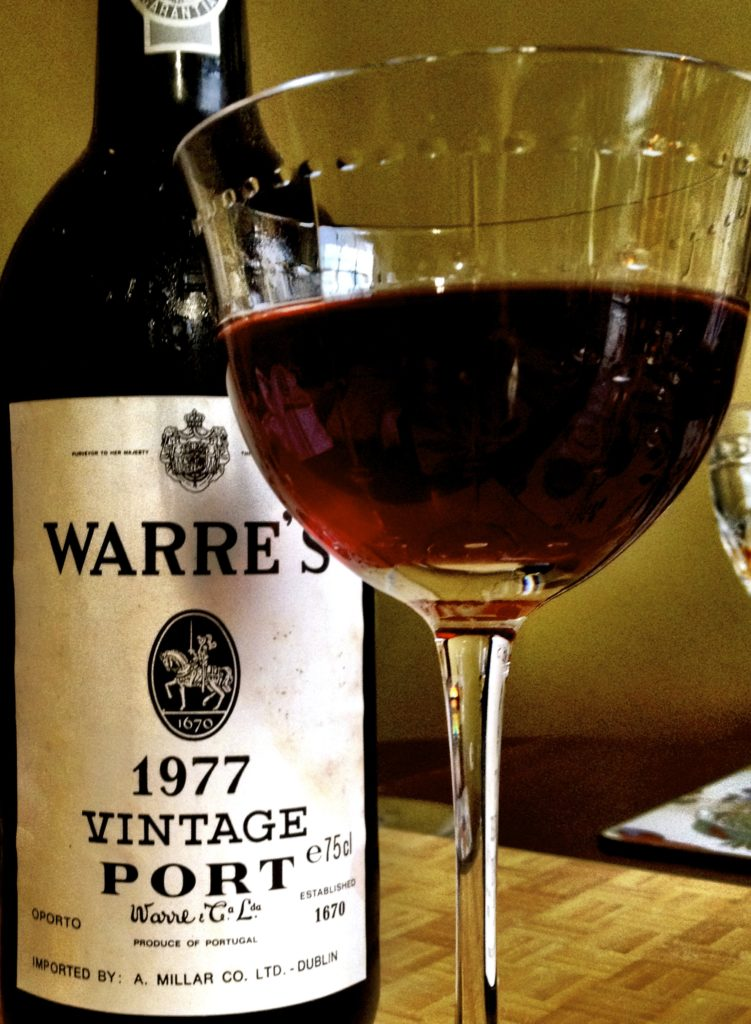 bottle of warre's port with half full wine glass